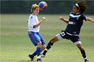Two Boys From Opposing Teams Going For The Ball